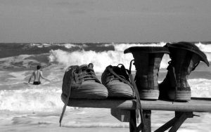 Two pairs of trainers on beach overlooking sea.